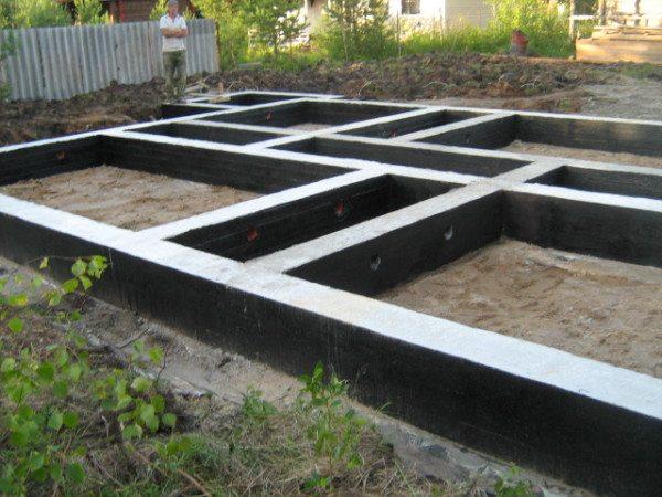 Готовый ленточный фундамент под дом из бруса, обработанный битумом для защиты от влаги
