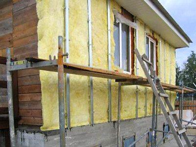 Любительское фото, показывающее процесс утепления дома из бруса с обрешеткой с последующей зашивкой
