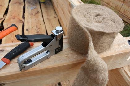 Стандартный уплотнитель из рулонной пакли фиксируют на материале при помощи степлера