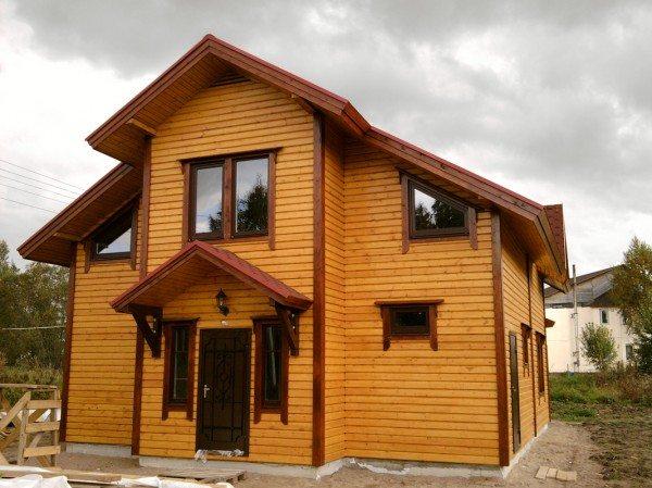 Двухэтажный дом обшитый имитацией бруса.