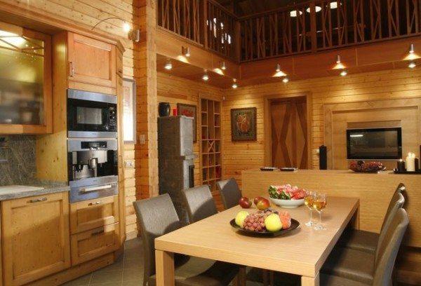 Этот интерьер кухни в доме из клееного бруса выполнен исключительно в древесных тонах, что делает его максимально «живым» и душевным