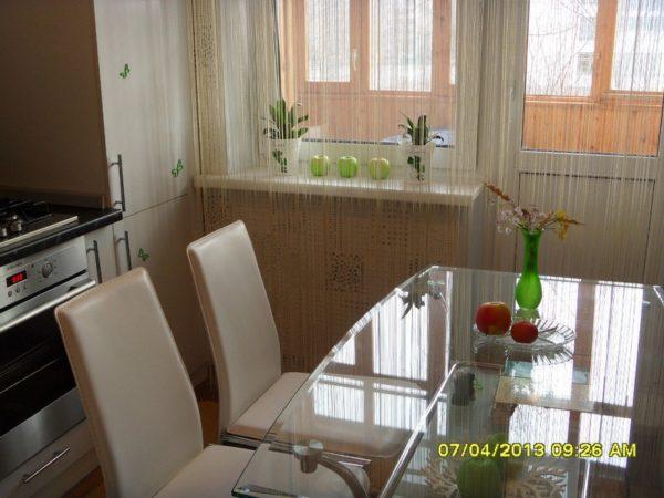 Даже немаленький стол со стеклянной столешницей оставляет ощущение пространства в кухне
