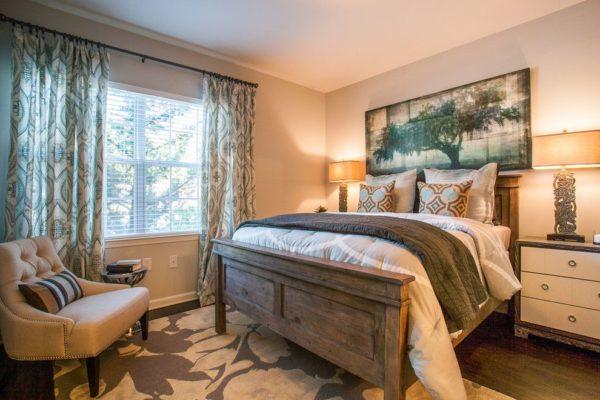 Спальня в стиле эклектика радует глаз спокойными тонами покрывала и узорчатыми подушками на массивной кровати