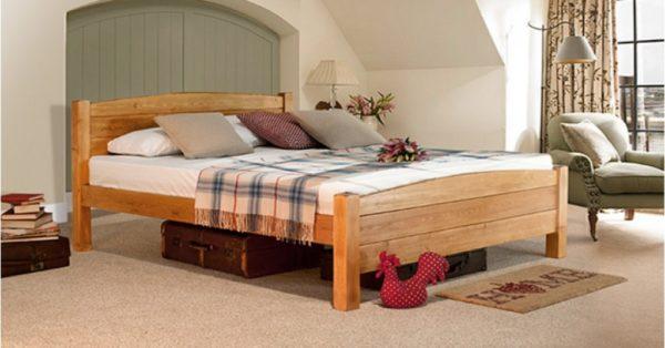 Теплые тона стиля кантри хорошо сочетаются с массивной кроватью из бруса. Поверх красуется характерный клетчатый плед или покрывало