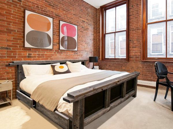 Простой до некоторой грубоватости лофт – идеальное сочетание строгих линий деревянной кровати на фоне кирпичных стен