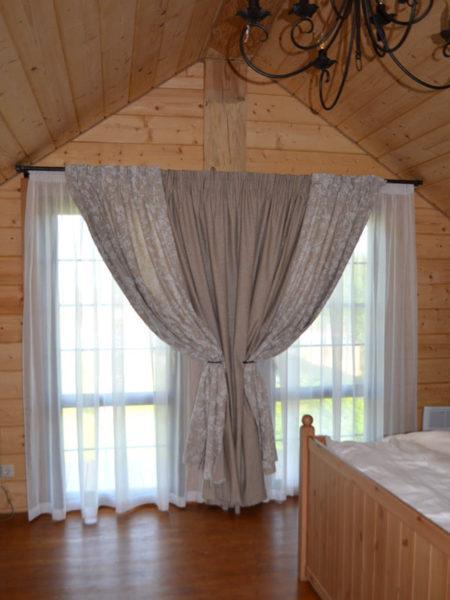 Объединение небольших окон одним карнизом с плотными шторами и легким тюлем позволяет визуально расширить пространство