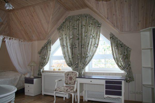 Нестандартную форму окна можно скрыть или наоборот подчеркнуть с помощью карниза и складок штор