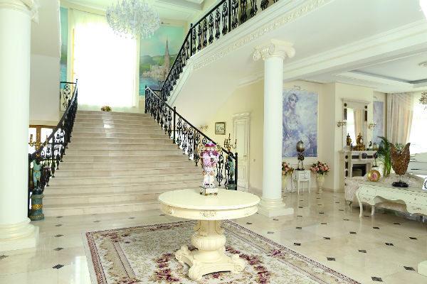 Стены площадки между ступенями были расписаны известными художниками, а их картины обклеены рамками из плинтусов. Потолок между этажами выложен гипсокартонными плитами с лепниной и украшен большой хрустальной люстрой.