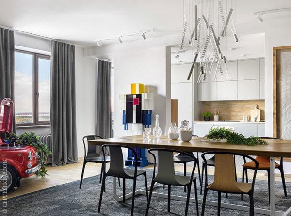 В столовой также есть картина-кроссворд с несуществующими ответами и робот. Монохромные фасады мебели кухни выполнены в сером цвете.