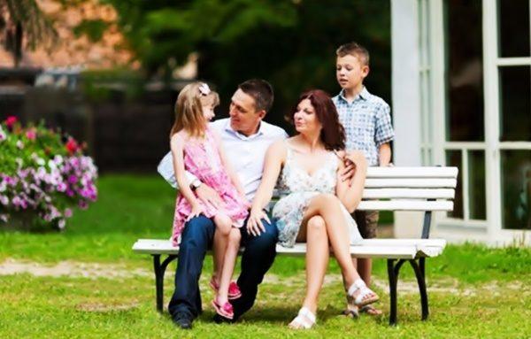 Отдых семьи на садовой скамейке