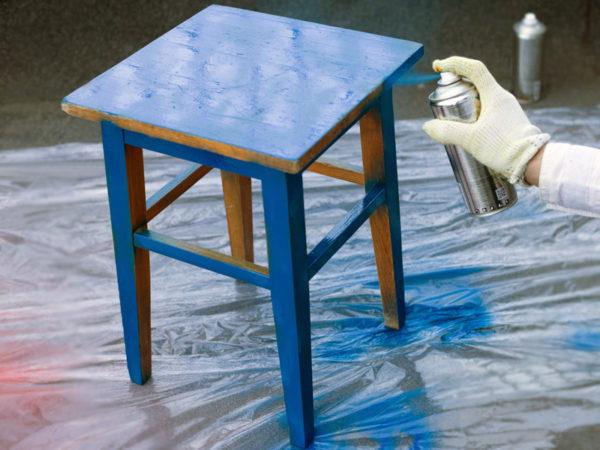 Процесс распыления краски на табурет