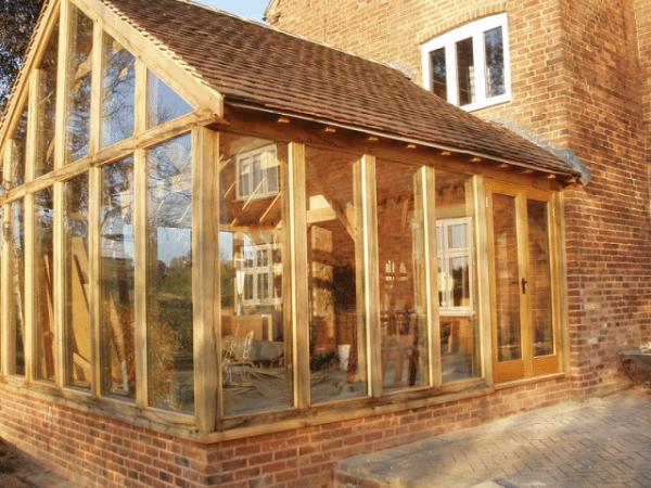 Интересно смотрится стекло в сочетании с деревянными опорами – это пристройка к кирпичному дому