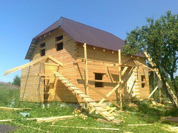 Любительское фото двухэтажного деревянного дома из брусьев с размерами 9 на 9