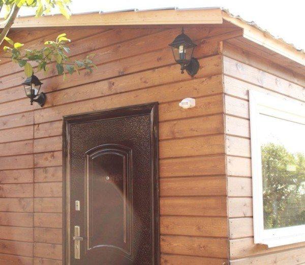 На фото показан дом с внешней обшивкой имитацией бруса.