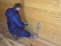 Осуществление конопатки брусовой стены паклей.